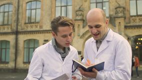 Two medical students discuss something near university stock footage