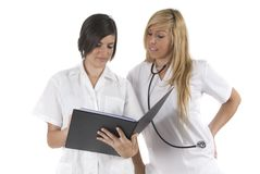 Two medical woman reading about theyr patients Royalty Free Stock Photos