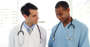 Two medical workers looking over file on clipboard. At the hospital stock video footage