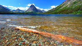 Two Medicine Lake Glacier National Park. Mount Sinopah rises over Two Medicine Lake on a gorgeous summer day in Glacier National Park stock footage