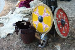 Two medieval round shield, late ancient roman burgh castle type helmet and plate leather armor, animal fur in background. Shot on summer medieval festival on Stock Photos