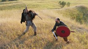 Two medieval warriors Viking are fighting with swords and shields. stock video footage