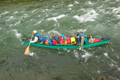 Two men in adventure canoe on rushing river rapids. Two men navigate an overloaded canoe through rushing rapids during an adventure on a wild Alaskan river Stock Image