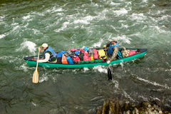 Two men in adventure canoe on rushing river rapids. Two men navigate an overloaded canoe through rushing rapids during an adventure on a wild Alaskan river Royalty Free Stock Image