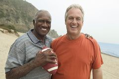 Two men with American football on beach (portrait) Stock Image