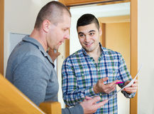 Two men at apartment doorstep Stock Photo