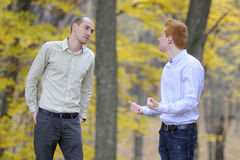 Two men arguing. Young people having dispute in nature Stock Photos