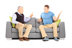Two men arguing seated on a sofa Stock Photo