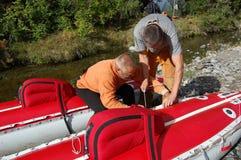 Two men assemble an inflatable catamaran. Royalty Free Stock Photos