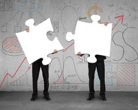 Two men assembling puzzles with business doodles background Stock Photography