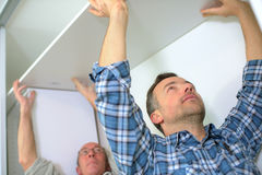 Two men assembling wardrobe Stock Image