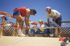Two men assist a child about to race in the annual Soap Box Derby in Venice, California Royalty Free Stock Images