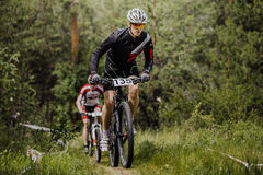 Two men athletes cyclist going uphill in woods Royalty Free Stock Image