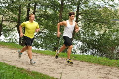 Two Men Athletes Running Through Park Stock Photos