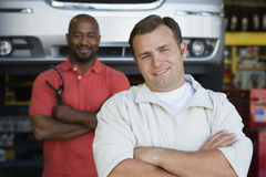 Two Men In An Auto Shop. Portrait of a happy confident male mechanics in auto shop Royalty Free Stock Images