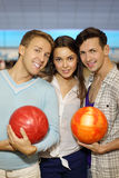 Two men with balls and girl in bowling club Royalty Free Stock Images