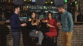 Two of the men in the bar he meets two women. Two girls at the bar stock footage