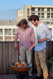 Two men barbecuing Royalty Free Stock Images