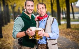 Men in bayrischer Tracht clinking glasses with beer stock photos