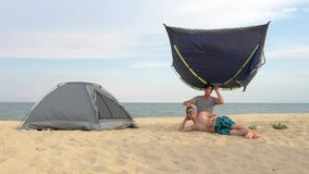 Two men on beach playing with tents. Installing tents in the camping near sea. stock video footage