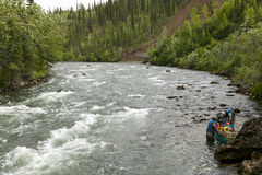Adventure canoeing rapids on an Alaskan river Royalty Free Stock Image