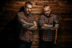 Two men with beards and tattoo. Two men with beards and tattoo posing over wooden wall. One of them holding axe Stock Photos