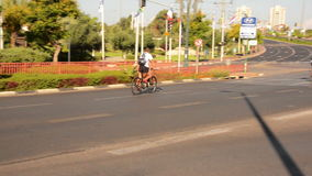 Two men bike on deserted city. Rishon LeZion, Israel - October 4,2014: Two unidentified men bike on deserted city road in the sunny morning. Once a year, on Yom stock footage