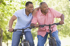 Two men on bikes outdoors smiling Stock Images