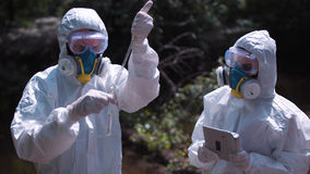 Two men in biohazard suits sampling water Stock Image