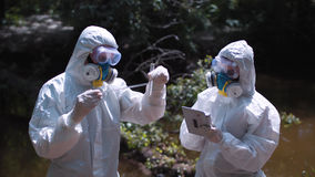 Two men in biohazard suits sampling water. Two men in biohazard suits and masks sampling water from a stream or river pipetting a sample into a test tube for stock image