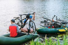 Two men in a boat with bicycles, June 11, 2018, Kaliningrad region, Russia, travelers on boats crossing, crossing the river with b stock photography