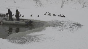 Two Men in the boat Cut Ice on the Frozen Lake. Saving swans and ducks on the frozen lake. Winter fishing, weather, savior stock video footage