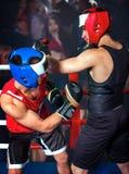 Two  men boxer wearing helmet  boxing. Two  men boxer wearing helmet and  gloves boxing . In background fans crowd Royalty Free Stock Photos
