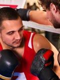 Two men boxer wearing helmet boxing indoor. Stock Photography