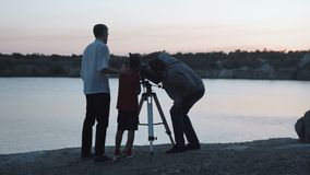 People exploring stars on shore of lake. Two men and boy using telescope watching stars on shore of lake in twilight stock video footage