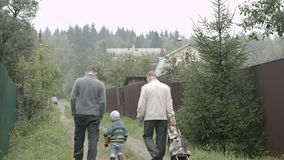 Two men and a boy walking in the countryside. Back view of father, son and grandpa walking along the road in the village. Old man rolling a trolley bag stock video footage