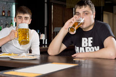 Two men on a boys night out drinking beer. Together at the counter in a bar or nightclub royalty free stock photography