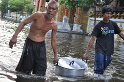 Two men are bringing free food for the refugees in a flooded street of Bangkok, Thailand, on 31 October 2011.  Royalty Free Stock Photos