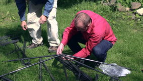 Two men building construction bower roof from metal parts stock footage