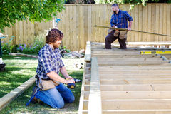 Two men building a deck. Two men constructing a deck royalty free stock image