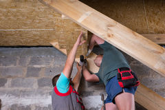 Two Men Building Stairs in Unfinished Basement Royalty Free Stock Images