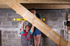 Two Men Building Stairs in Unfinished Basement stock photo