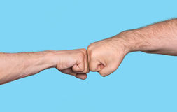 Two men bumping fists. Isolated on blue background Stock Image
