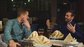 Two men on a business dinner, drink wine. A business meeting between two men in the restaurant stock video