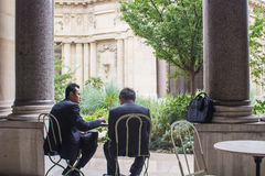 Two men in business suits confer at a cafe table in the courtyar Royalty Free Stock Images