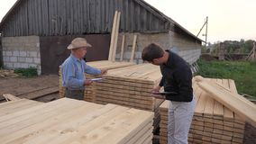Two Men of a Businessman Inspect And Choose A Ready Wooden Board. The buyer and the seller, an adult man and a young businessman, conduct an inspection as packed stock video footage