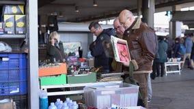 Two men buy vinyl records at a flea market