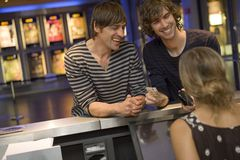 Two men buying a movie ticket at the box office. Stock Photo