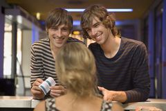 Two men buying movie tickets at the box office. Royalty Free Stock Photos
