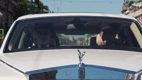 Two men in the cabin of a white Rolls Royce. Driving on city streetn stock footage